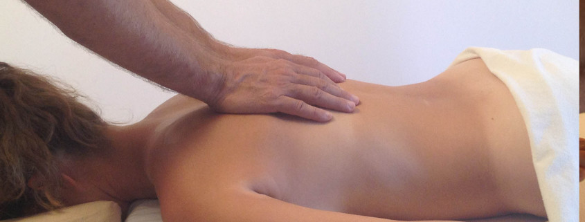 Two hands applying massage to the back.